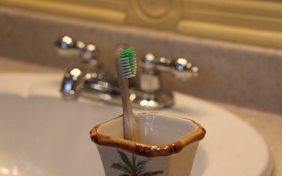 Brosse à dent écologique en bambou dans un support à brosse à dents devant un lavabo